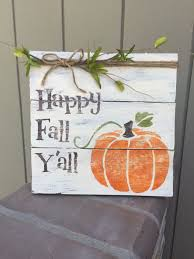 "Wood sign with pumpkin says ""Happy Fall Y'all"""